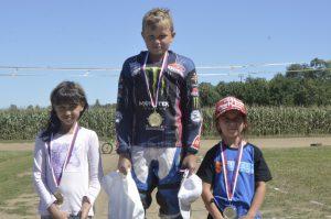 První závody, první vítězství, Kostěnice v červenci 2018 stojí na pódiu kategorie Junioři Flat Track: Denisa Maclová, Dominik Hrbek a Ela Kňávová